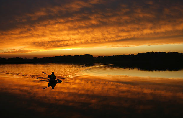 A man paddles his kayak across the calm surface of Lake Chillisquaque, White Hall, Pennsylvania