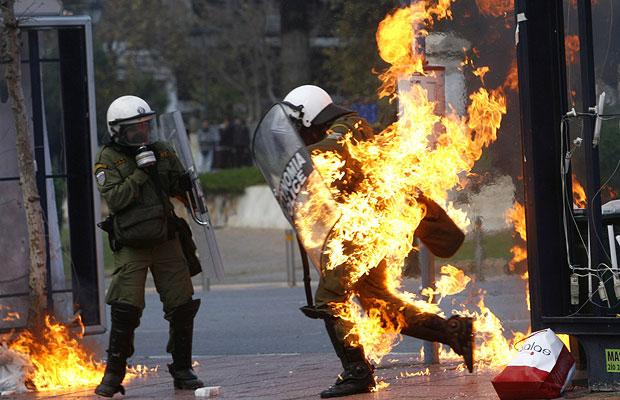 a-riot-policeman-in-flames-runs-to-escape-during-a-riot-in-athens