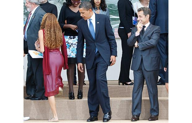 US President Barack Obama and France's President Nicolas Sarkozy look on as Brazil's Mayora Tavares walks by for a family photo at the G8 summit in L'Aquila, Italy