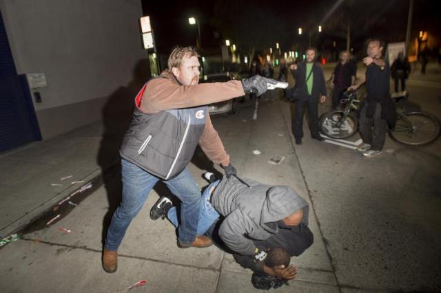 An undercover police officer, who had been marching with anti-police demonstrators, aims his gun at protesters after some in the crowd attacked him and his partner in Oakland